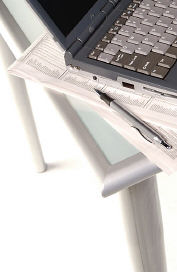Black laptop computer and pen on top of newspapers