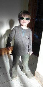 Boy wearing wellies and sunglasses