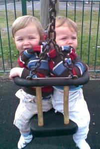 Twins sitting in a swing together