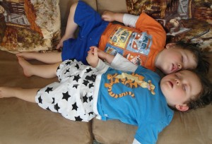 Twins asleep holding hands