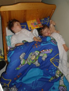 Twin toddlers in bed asleep together